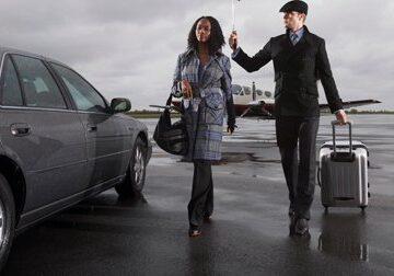 Professional driver holding umbrella